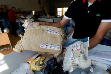 A Palestinian worker displays items sent by mail eight years ago, after Israel allowed the letters and goods into the West Bank from Jordan, where they were being held, Jericho