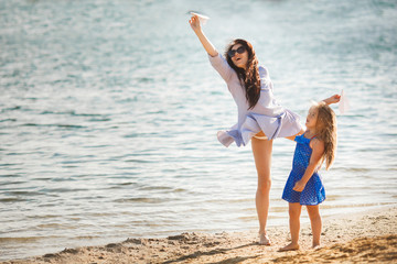 Young mother and her cute daughter at the sea side launching paper aircrafts in the air and laughing. Cheerful family at the beach