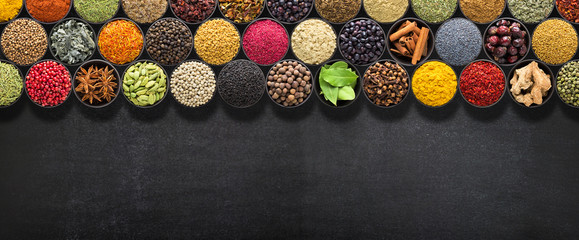 Spices and herbs for European food. Seasoning on  black table with space for recipe or text.