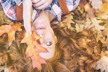 red hair beauty lying in autumn leaf