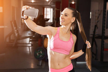 joyful girl with a long ponytale wearing pink and black professional sportswear making selfie photo at the gym. concept of modern peoples lifestyle