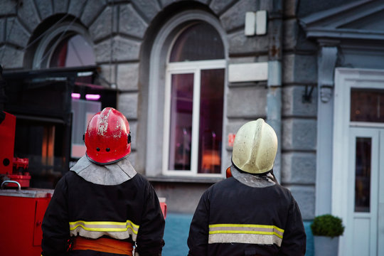 Two silhouette of firefighters in special fireproof uniform and personal protective eqipment on emergency call
