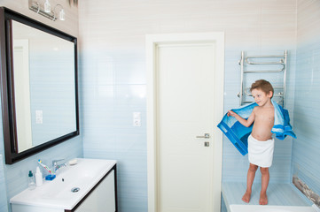 cute healthy little boy dry off his body with blue towel in morning bathroom