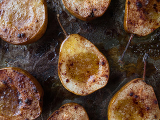 baked pears with maple syrup and cinnamon on wax paper flat lay
