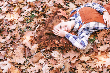 young happy redhair beauty in leaves