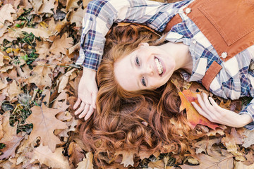 young beauty red hair in leaf