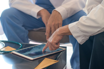 Digital health and teamwork concepts. Doctor physician work together with Anesthesiologists using tablet to view medical x-ray images of patient in hospital.