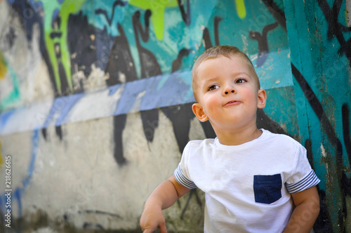 4cfa9cfbc9be8 Two-year-old baby boy in hip hop style clothes sitting under a wall ...