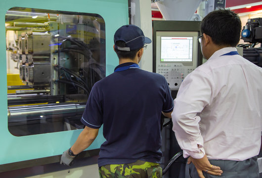 Industrial technician operate injection molding press machine. Industrial plastic manufacturing