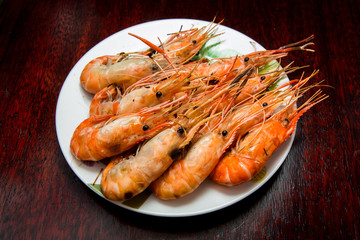 Grilled river shrimps on white plate on wooden background, Thai style food