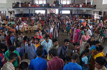 Flood victims wait for food inside a college auditorium, which has been converted into a temporary relief camp, in Kochi