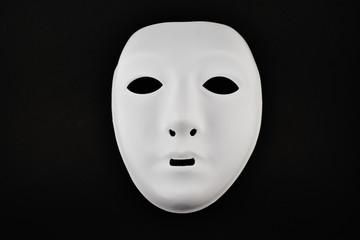 Plastic white face mask stock images. White mask on a black background. Plastic human mask