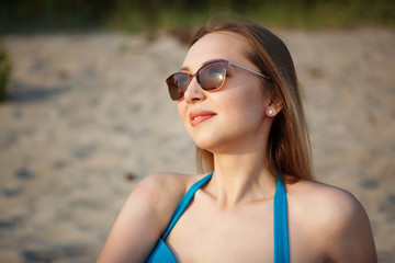 Young pretty woman in a blue swimsuit and sunglasses