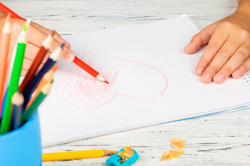 Hand of children drawing red heart with colored pencil on white paper on wooden table.