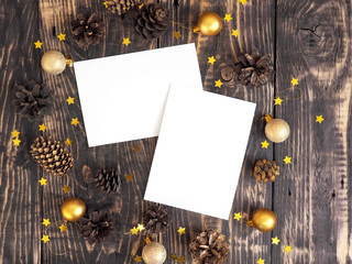 Branding mock-up two greeting cards. Christmas new year card mockup with fir cones, christmas golden balls and confetti stars on dark wooden background. Top view