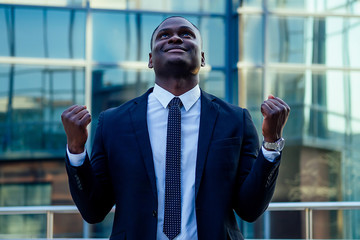 a handsome African American man in a black stylish suit and a white shirt rejoicing in success and thanking God against the background of city landscapes glass business centers. a good deal concept