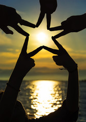 Many hands connecting to star shape at sunset, Teamwork Concept