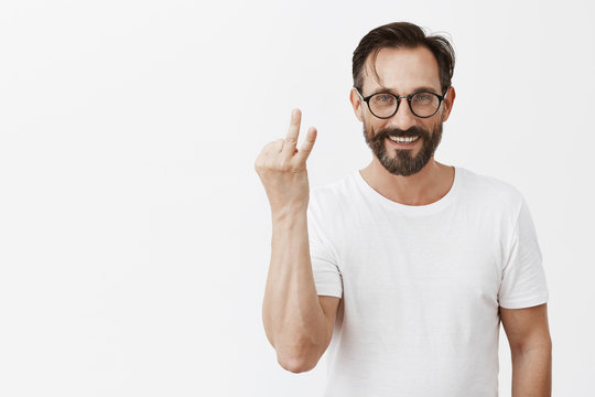 Two reasons why I like you. Studio shot of charming happy and carefree adult man in glasses and t-shrit, showing twice sign and smiling broadly, standing over gray background numbering points