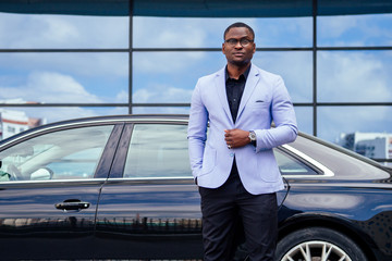 successful businessman handsome African American man in a stylish suit in a blue jacket standing in front of a cool new black car on the street
