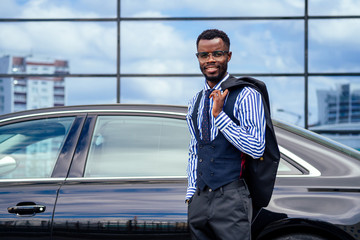 successful businessman handsome African American man in a stylish suit in gray jacket and glasses standing in front of a cool new black car on the street