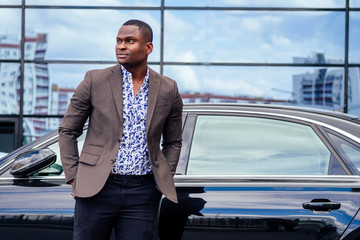 successful businessman handsome African American man in a stylish suit in brown jacket and glasses standing in front of a cool new black car on the street
