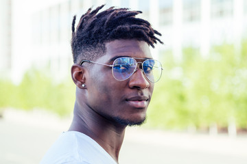 portrait stylish and handsome African student American man with cool dreadlocks and earringin the ear diamond fashion look walking on the street