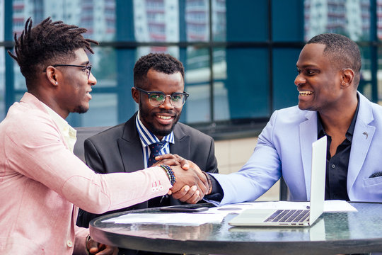 A group of three stylish African American businessman friends entrepreneurs fashion business suits meeting sitting at table and handshaking in a summer cafe outdoors. concept of successful good deal