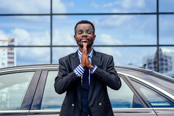 successful businessman handsome African American man in a stylish suit in jacket black and glasses standing in front of a cool new black car and meditating practicing yoga on the street