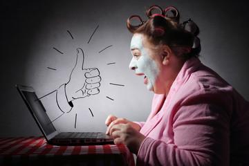 femme drôle avec bigoudis surfant son ordinateur portable avec dessin de pouce levé