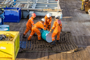 Offshore workers preps oil drum on cargo net on a construction barge at oilfield - fototapety na wymiar