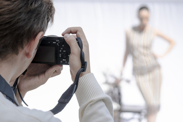 Men's hands hold the camera. The model is posing.
