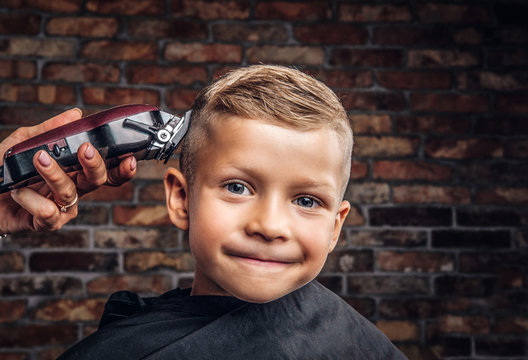 Close-up portrait of a cute smiling boy getting haircut against a brick wall.