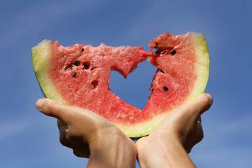 sweet summer love/ slice of watermelon with symbol  heart in his hands against the sky