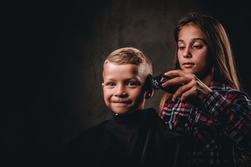 The older sister cuts her little brother with a trimmer against the dark background. Cute preschooler boy getting a haircut.
