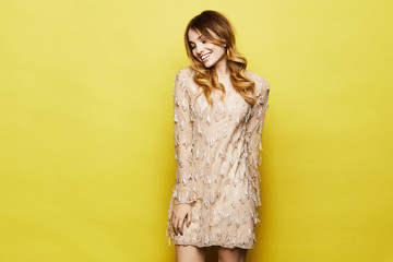 Fashionable and emotional blonde model girl with bright makeup and with shiny smile, in stylish peach dress posing in studio at yellow background