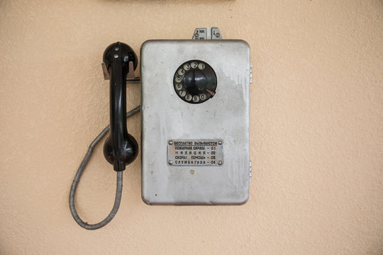 Old retro phone on a wall of gray.