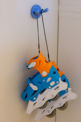 Roller skates hanging on a blue hook