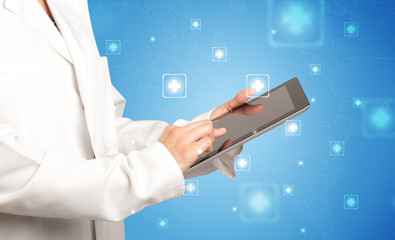 Female doctor holding tablet with blue background and crosses