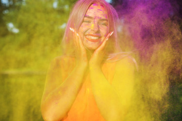 Laughing young model posing with exploding yellow paint at summer Holi festival