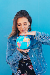 Young woman holding a globe between her hands