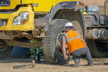 Driver changes the blown wheel on the construction site