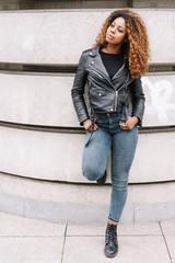 attraktive frau mit lederjacke und jeans lehnt an einer wand