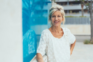 Relaxed senior woman stood in city