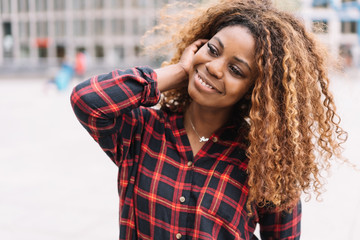 Relaxed happy young African woman in town