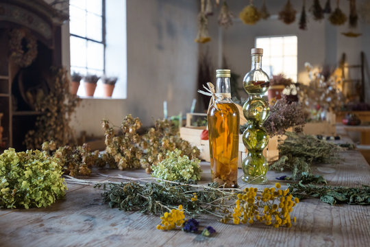 Two bottles with oil on a table with dried herbs and flowers