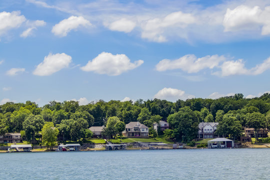 Upscale homes with boat docks built along the edge of a lake with tall green trees under a blue sky with fluffy clouds