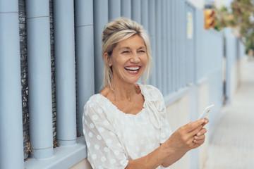 Mature blonde laughing woman using mobile phone