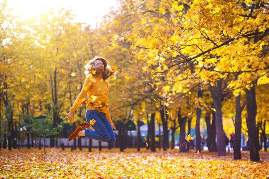 girl in a park throws yellow leaves