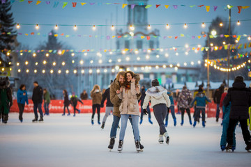 Young couple in love Caucasian man with blond hair with long hair and beard and beautiful woman have fun, active date skating on ice scene in town square in winter on Christmas Eve