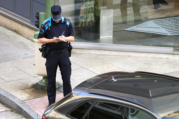 policeman writing fine ticket for car bad parking